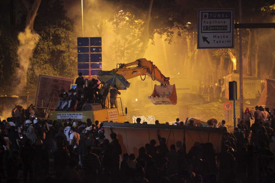 Anti-government protesters behind barricades and on an excavator clash with riot police as they try to march to the office of Turkey's Prime Minister Tayyip Erdogan
