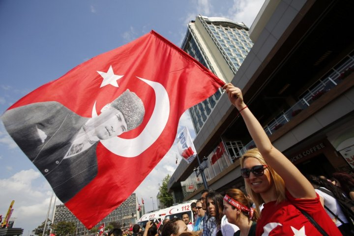 A demonstrator waves a Turkish flag with a portrait of Mustafa Kemal Ataturk during an anti-government protest