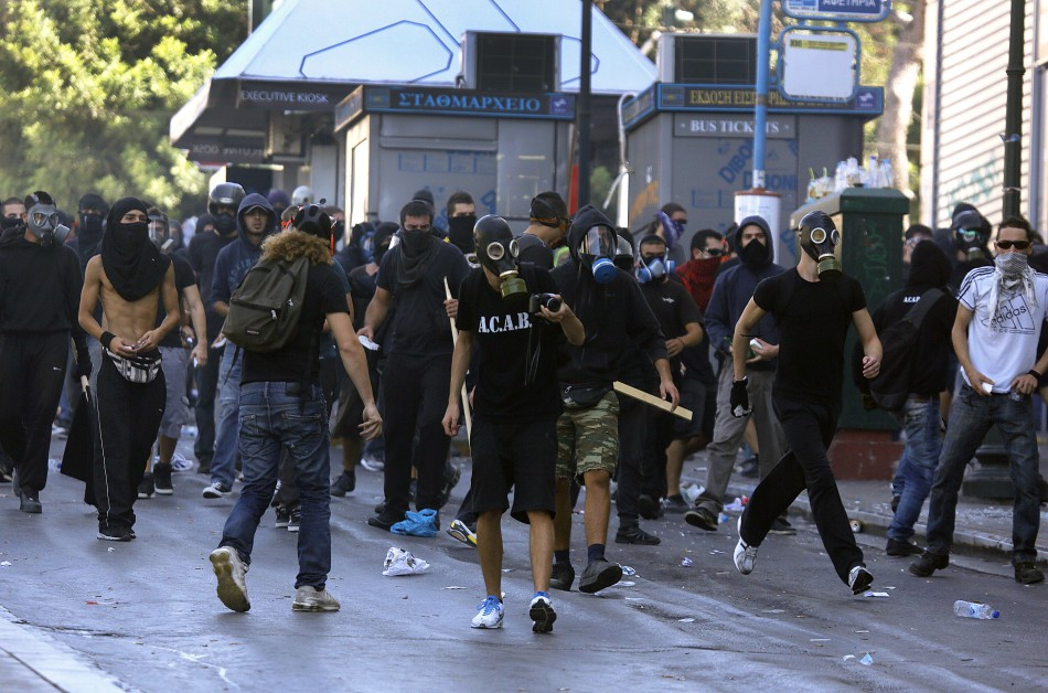 Hooded youths move towards riot police in Athens' Syntagma square during a 24-hour labour strike September 26, 2012. Greek police fired teargas at hooded youths hurling petrol bombs and stones as tens of thousands took to the streets in Greece's biggest a