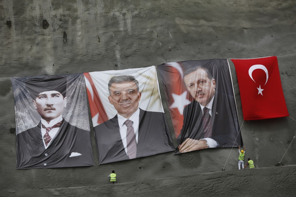 Workers hang portraits of modern Turkey's founder Mustafa Kemal Ataturk (L), President Abdullah Gul (2nd L) and Prime Minister Tayyip Erdogan