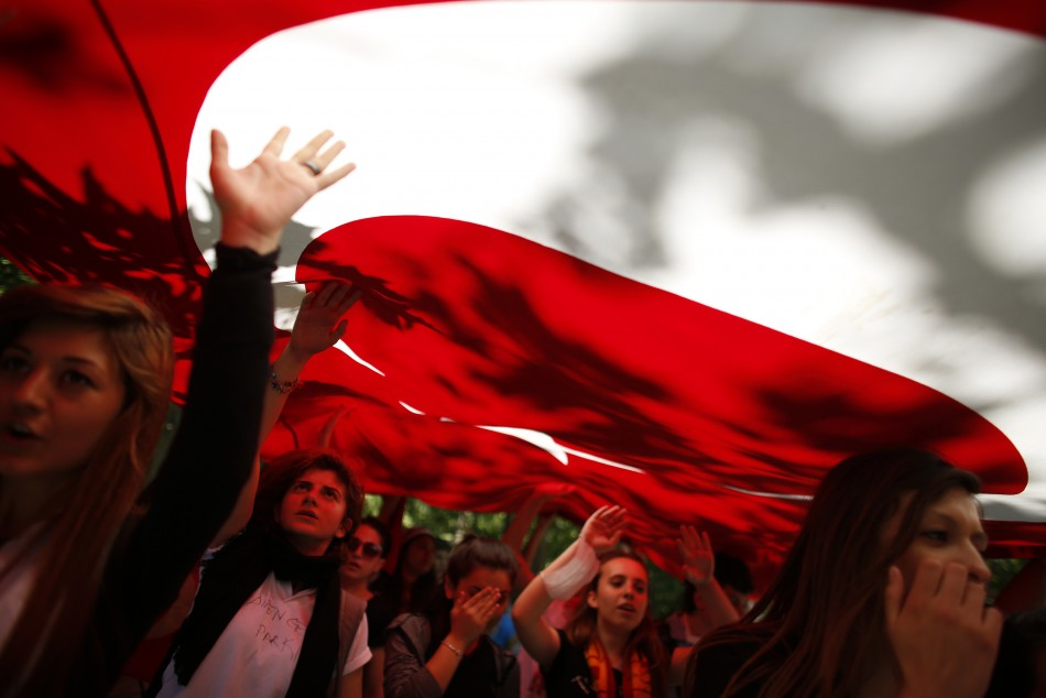 Protesters carry the Turkish flag and shout anti-government slogans