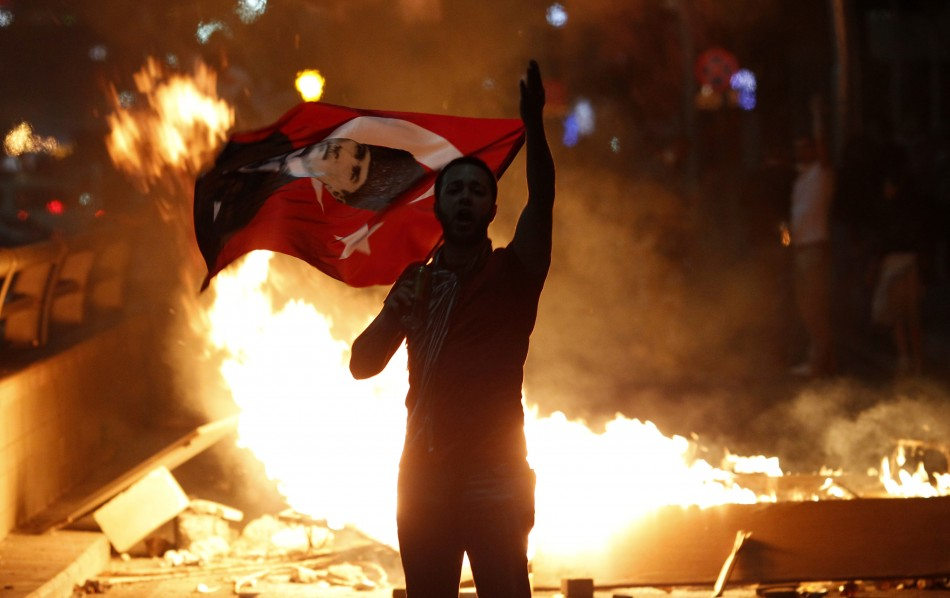 An anti-government protester holds a Turkish national flag with a portrait of Mustafa Kemal Ataturk