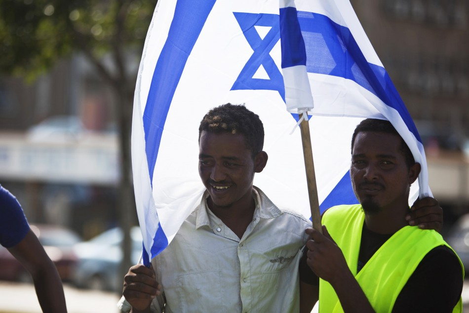 African migrants from Eritrea hold an Israeli flag during a protest near the Ministry of Defence in Tel Aviv
