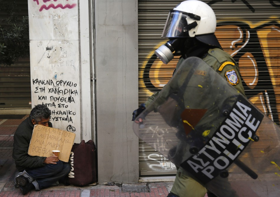 A riot policeman walks by a homeless beggar during a rally in Greece (Photo: Reuters)