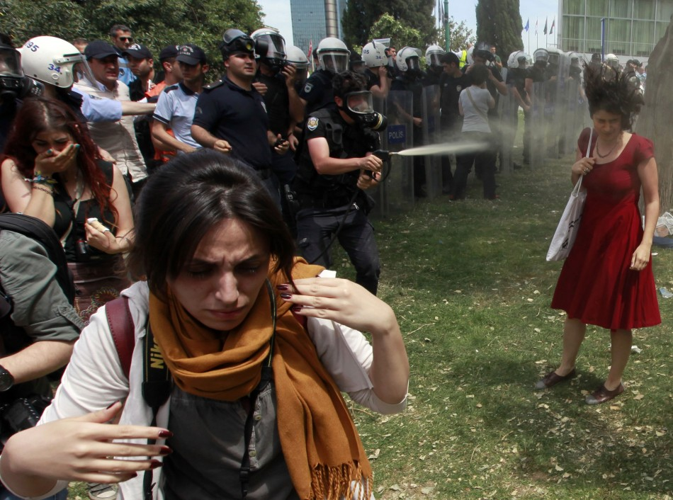 An image of a Turkish riot policeman firing tear gas at a protester during a demonstration against the destruction of trees in a park brought about by a pedestrian project, in Taksim Square in central Istanbul.