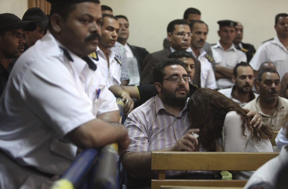 Friends of Egyptian suspects react as they listen to the judge's verdict at a court room during a case against foreign non-governmental organisations (NGOs) in Cairo
