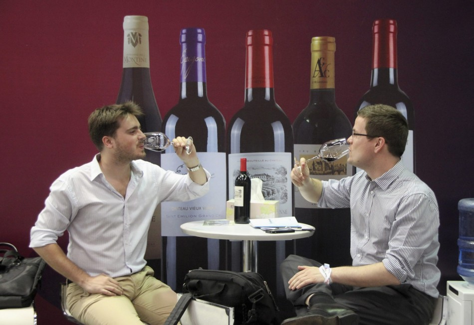 People taste French wine at a wine expo in Beijing