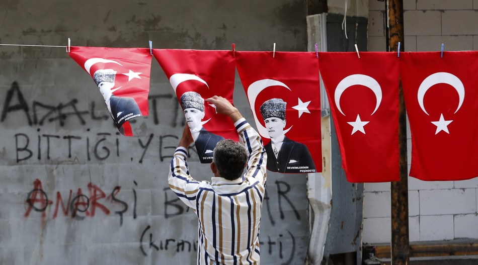 A man displays Turkey's national flags and flags printed with portraits of Mustafa Kemal Ataturk