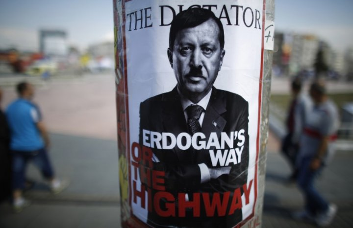 People walk past a poster depicting Turkish Prime Minister Tayyip Erdogan that has been pasted by demonstrators at Taksim Square in Istanbul