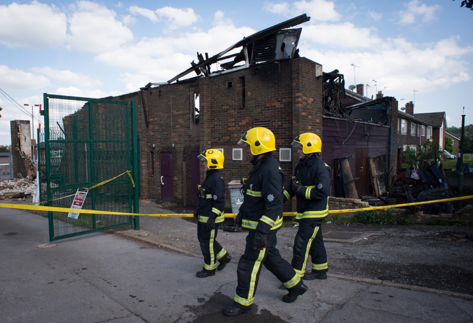 Firefighers walk past the Somali Bravanese Welfare Association in north London (Reuters)
