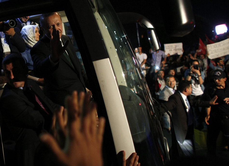Turkey's Prime Minister Tayyip Erdogan (2nd L) waves to supporters after arriving at Istanbul's Ataturk airport