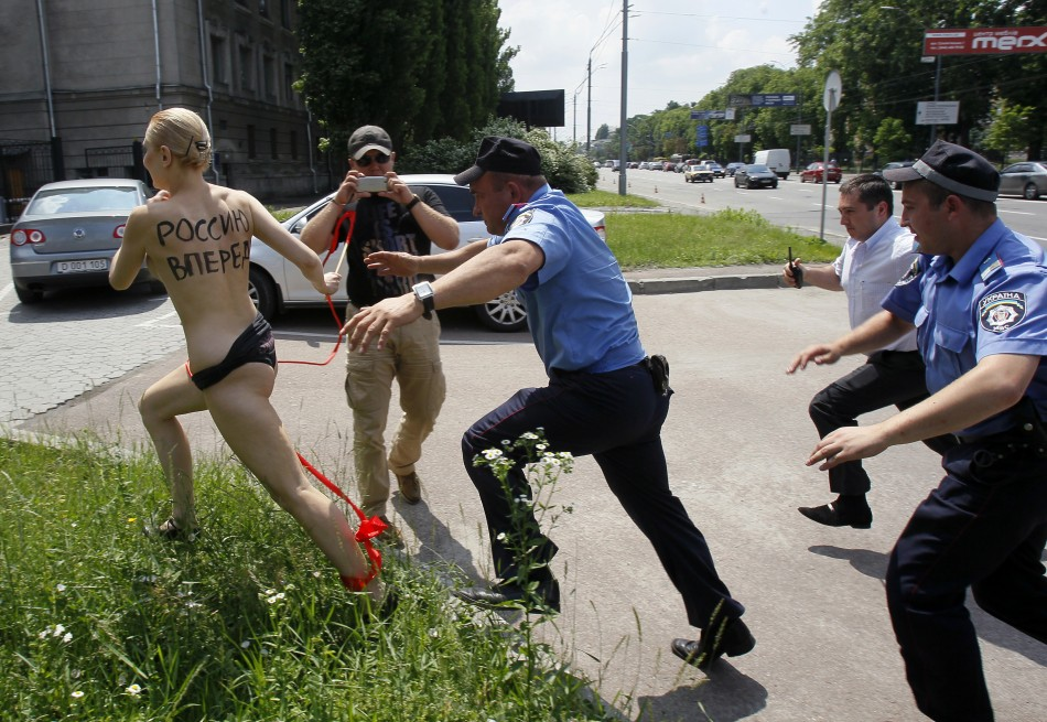 Interior ministry officers and security chase Femen activist in Kiev