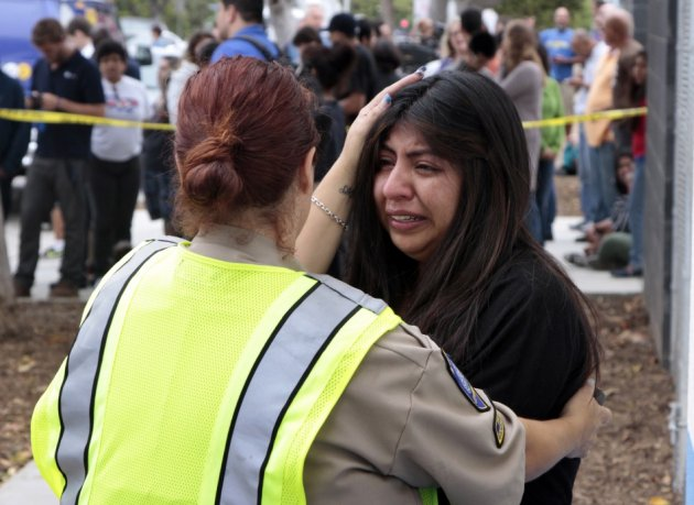 A women is comforted by a traffic officer near Santa Monica College following a shooting on the campus in Santa Monica.