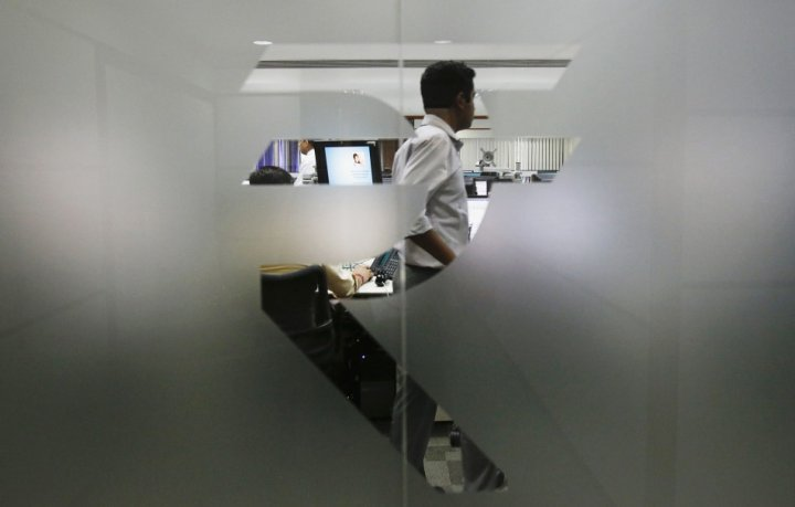 A currency trader is pictured through the symbol for the Indian Rupee on the floor of a trading firm in Mumbai, in May, 2013. (Reuters)