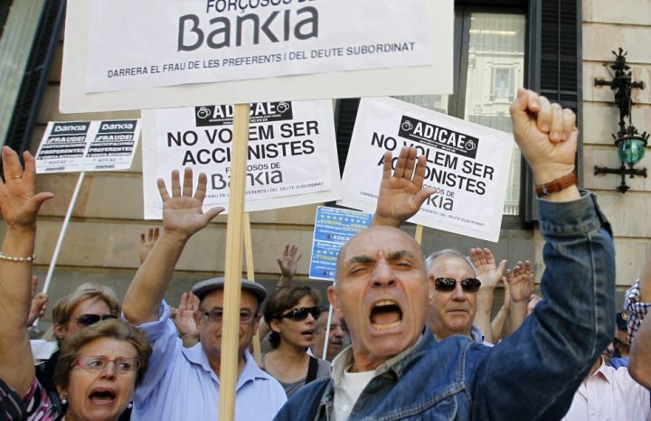 Junior debt holders of Bankia take part in a protest outside Spain's regional government office in Barcelona June 6, 2013. The signs read,