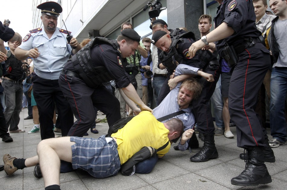 Policemen break up a fight between a gay rights activist and an anti-gay rights activist (in yellow) during a protest against a proposed new law (Reuters)
