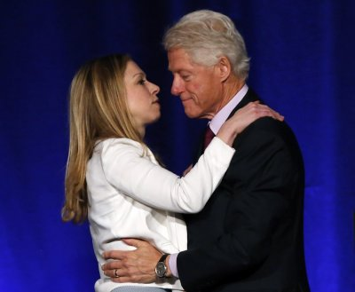 Former U.S. president Bill Clinton is congratulated by his daughter Chelsea Clinton for his nomination as Father of the Year at a lunch in New York, June 11, 2013.