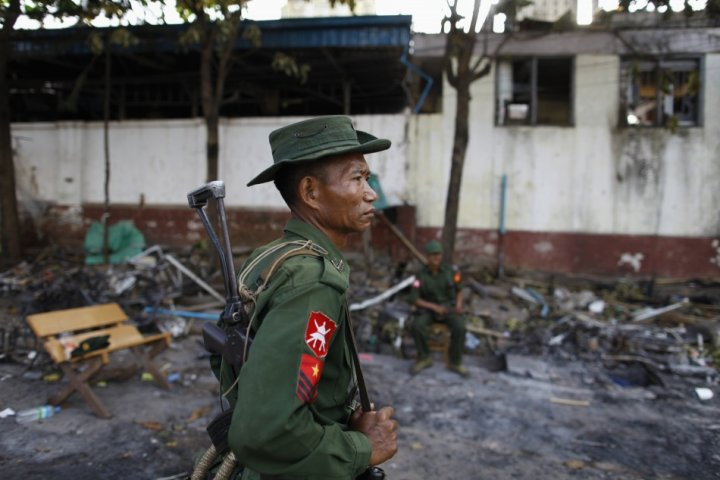 A soldier stands guard in front of a mosque that was burnt during a riot between Muslims and Buddhist in Lashio