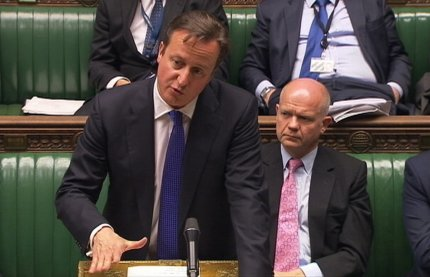 Britain's Prime Minister David Cameron, flanked by Foreign Secretary William Hague (R)