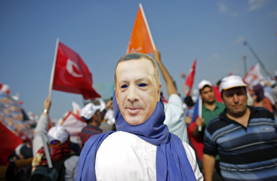 A supporter wears a mask showing Turkish Prime Minister Tayyip Erdogan during a rally of ruling AK party in Istanbul