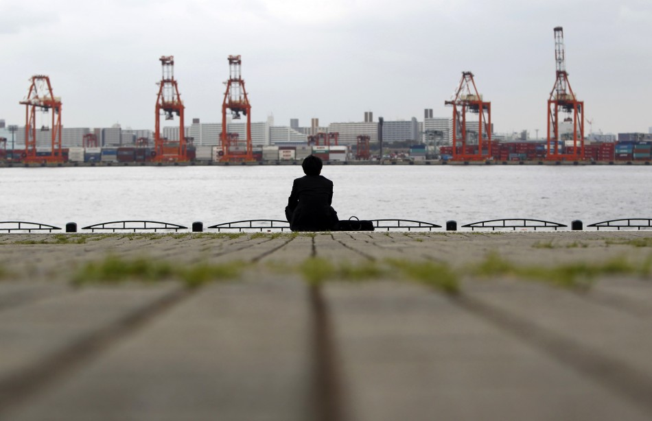 a businessman sitting near a cargo area at a port in Tokyo