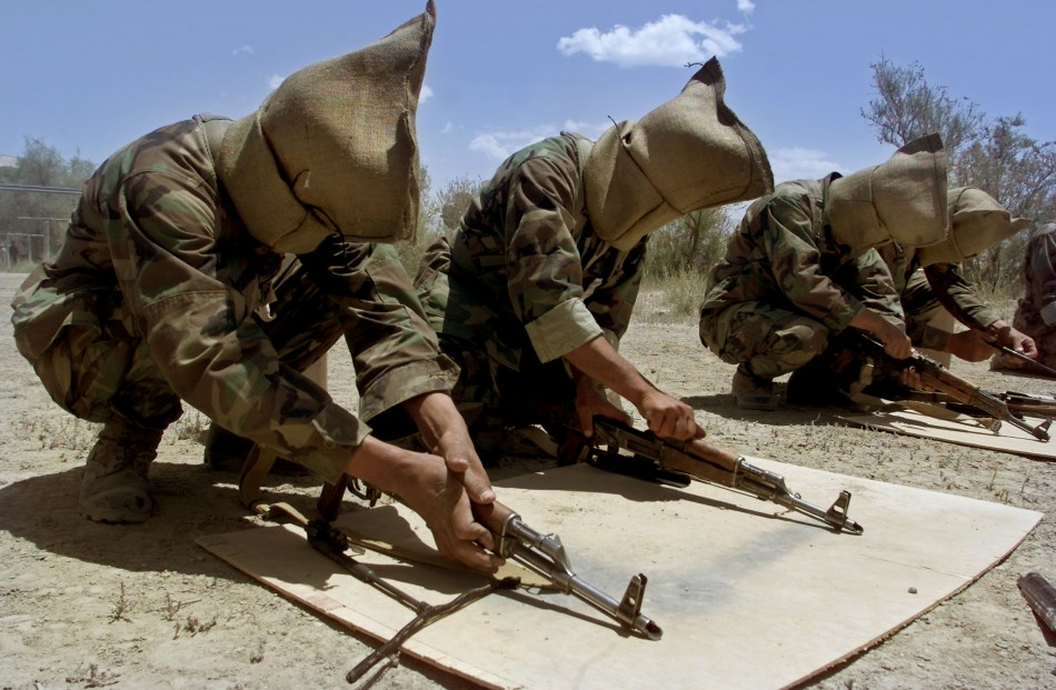 Afghan soldiers with sacks on their heads disassemble their machineguns during training by U.S.special forces