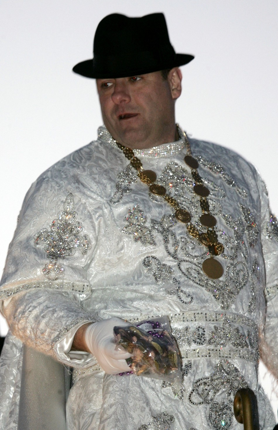 James Gandolfini, in unfamiliar getup, throws beads to revellers at a New Orleans street parade