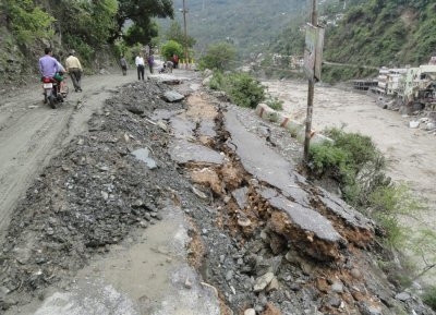 People walk along a damaged road after heavy rains in the Himalayan state of Uttarakhand June 17, 2013.