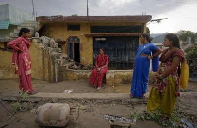 Residents stand outside their houses that were damaged due to floods in Srinagar, in the Himalayan state of Uttarakhand June 19, 2013.
