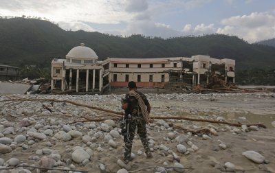 A member of the rescue operation team of Sashastra Seema Bal SSB or Armed Border Force walks towards the officers training centre damaged by floods at their campus in Srinagar in the Himalayan state of Uttarakhand June 19, 2013.