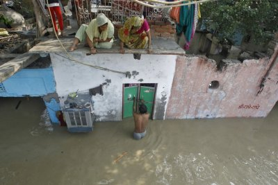 A man unlocks the door of his flooded house as other residents watch after a rise in the water level of river Yamuna in New Delhi June 19, 2013.