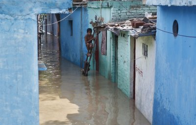 A boy sits on a ladder next to his flooded house with the rising water level of river Yamuna after heavy monsoon rains in New Delhi June 19, 2013
