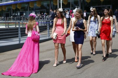 Women look at the dress of a race goer on the second day of the Royal Ascot