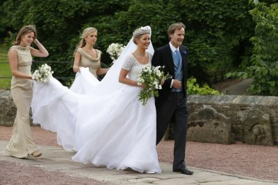 Melissa Percy is escorted by her father, Ralph Percy, the Duke of Northumberland, and bridesmaid Chelsey Davy 2nd L as she arrives for her wedding to Thomas van Straubenzee, at St Michaels Church in Alnwick, northern England June 22, 2013.