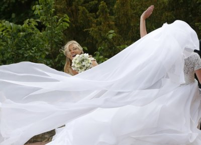 Bridesmaid Chelsy Davy reacts as wind blows the wedding dress of Melissa Percy