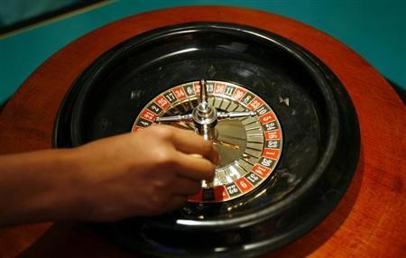 A dealer spins a roulette wheel at a mock casino where no money was used during the launch ceremony of