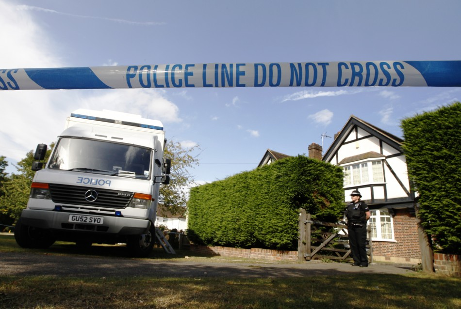 A police officer stands by a cordon close to the house of Saad al-Hilli and his family in Claygate