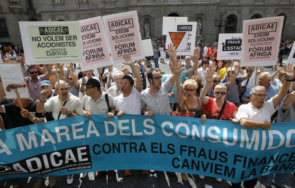People take part in a protest against banking system in front of Generalitat Catalunya Palace (regional government) in Barcelona June 22, 2013. The banner reads,