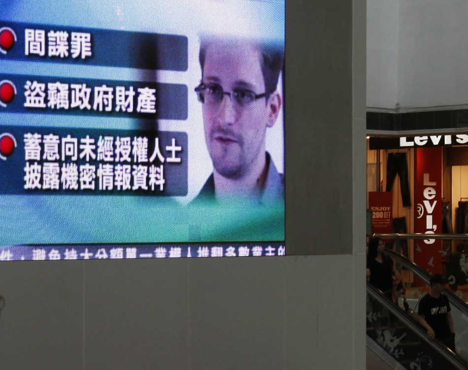 A monitor broadcasts news on the charges against Edward Snowden