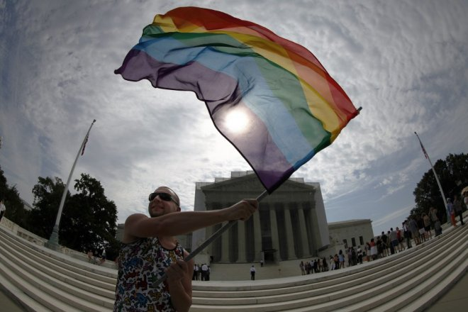 Gay marriage supporter Vin Testa waves a rainbow flag in anticipation of U.S. Supreme Court rulings