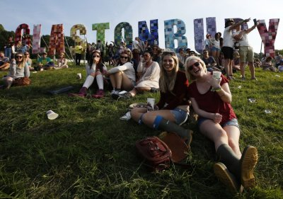 Festival goers watch their friends play rounders