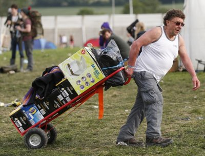A festival goer wheels in a mobile toilet and crates of beer
