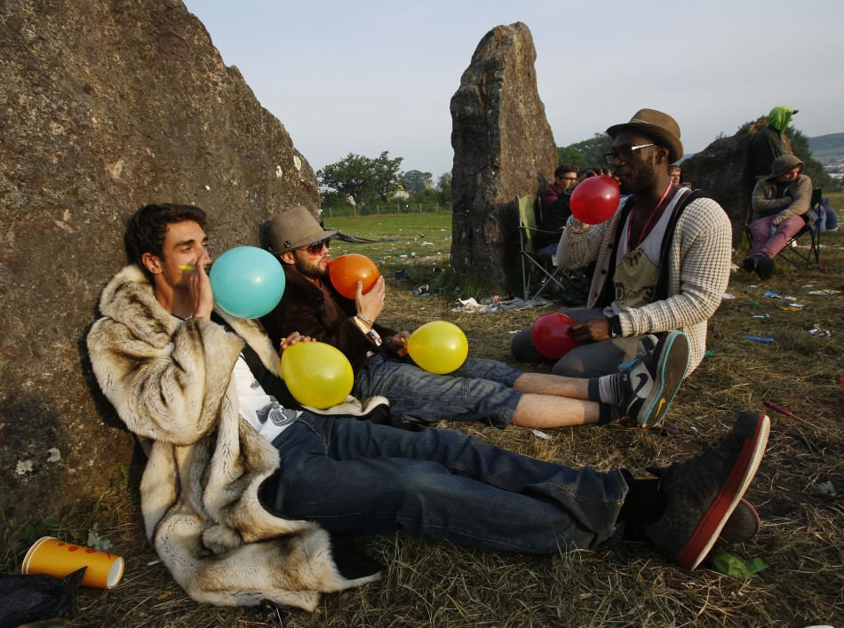 Festival goers inhale laughing gas at sunrise at the stone circle