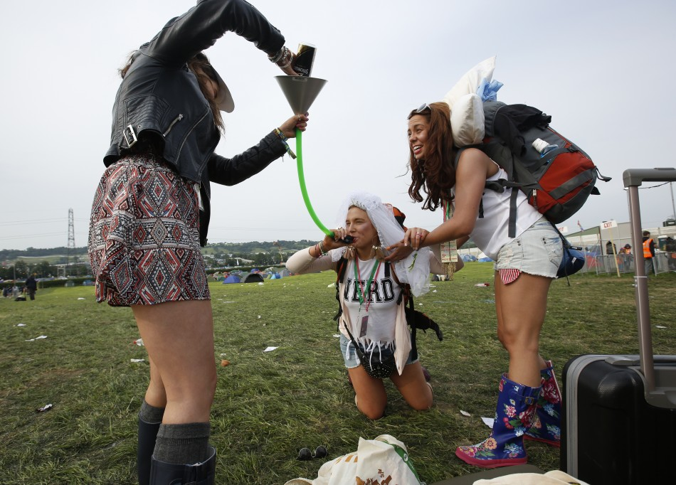 Bride-to-be Lizzie Chapman, 23, drink cider through a funnel on arriving at Glastonbury, where she celebrates her hen night