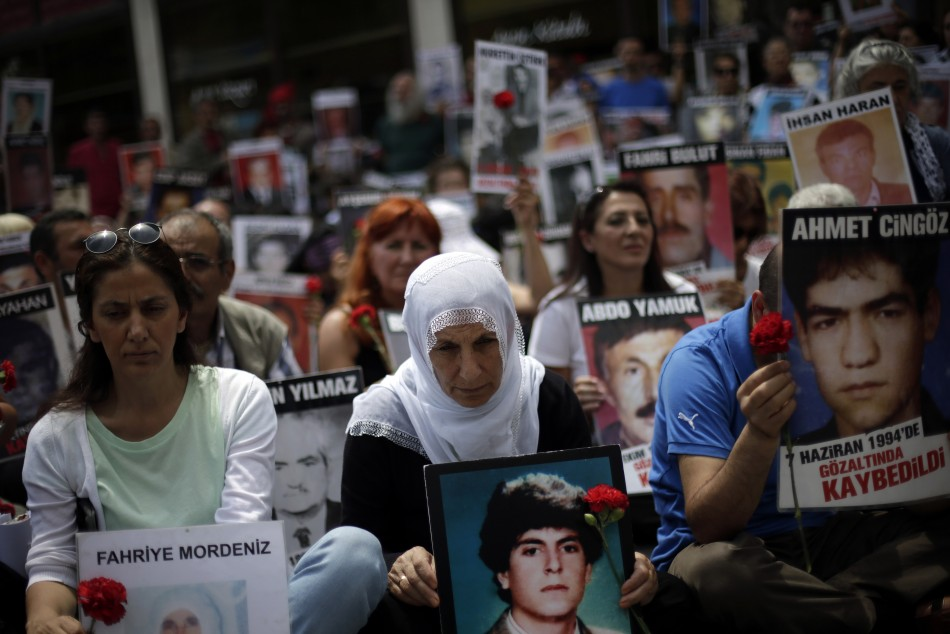Turkish Kurdish people hold pictures of their relatives who were killed in clashes between Kurdistan Workers' Party (PKK) guerrillas and Turkish security forces