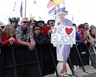 A member of the crowd holds a lifesize cutout of Queen Elizabeth at the Pyramid Stage at Glastonbury music festival at Worthy Farm in Somerset, June 29, 2013.