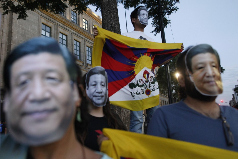 Activists wearing masks in the image of China's President Xi Jinping hold Tibetan flags as they protest against Xi's official visit to Mexico outside the National Palace in Mexico City June 4, 2013. (Photo: REUTERS)