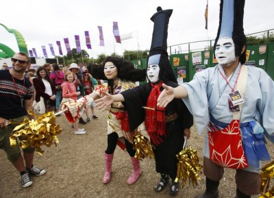 Japanese performance artists Masanori Takeuchi shake hands with festival goers