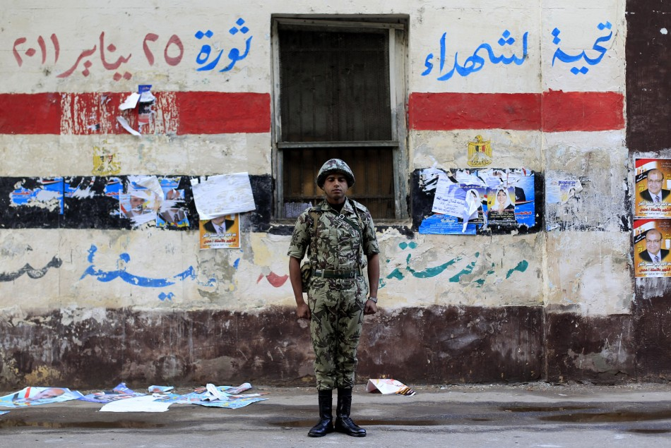 An Egyptian soldier stands guard in front of a polling station in Cairo