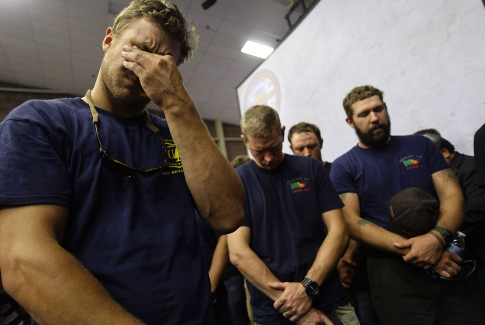 Hotshot firefighters mourn during a moment of silence for the 19 firefighters who died in the fast-moving fire (Reuters)